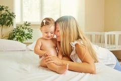 Moeder en baby in een luierspel die op een bed binnen koesteren Royalty-vrije Stock Afbeeldingen