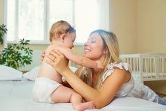 Moeder en baby in een luierspel die op een bed binnen koesteren Stock Fotografie