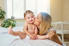 Moeder en baby in een luierspel die op een bed binnen koesteren Stock Foto's