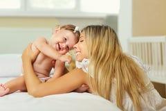 Moeder en baby in een luierspel die op een bed binnen koesteren Royalty-vrije Stock Foto's