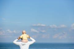 Moeder en baby geknuffel op het strand Stock Afbeeldingen