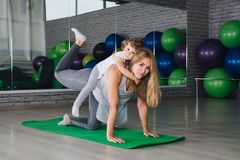 Moeder en baby girl do exercises samen in de gymnastiek royalty-vrije stock foto