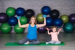 Moeder en baby girl do exercises samen in de gymnastiek stock foto's