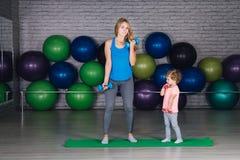 Moeder en baby girl do exercises samen in de gymnastiek stock foto