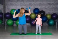Moeder en baby girl do exercises samen in de gymnastiek stock afbeelding