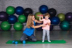 Moeder en baby girl do exercises samen in de gymnastiek royalty-vrije stock foto's