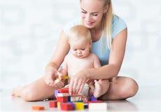 Moeder en baby het spelen met blokken Stock Foto's