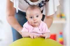 Moeder en baby het spelen op geschiktheidsbal Royalty-vrije Stock Foto