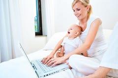 Moeder en baby met laptop Stock Foto's