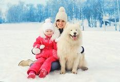 Moeder en baby met witte Samoyed-hond samen in de winter Royalty-vrije Stock Afbeeldingen