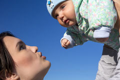 Moeder en baby op blauwe hemelachtergrond Stock Afbeelding
