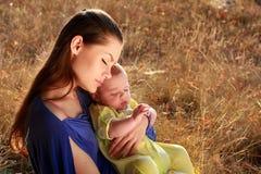 Moeder en baby op gras stock afbeeldingen