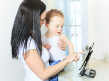 Moeder en babyjongen die digitale tablet binnen gebruiken Royalty-vrije Stock Foto's