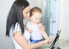 Moeder en babyjongen die digitale tablet binnen gebruiken Stock Foto's