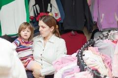 Moeder en babymeisje bij klerenwinkel Stock Fotografie