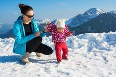 Moeder en babymeisje in de wintersneeuw stock foto