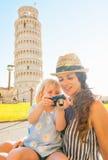 Moeder en babymeisje die foto's in camera controleren Stock Afbeeldingen