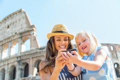 Moeder en babymeisje die foto's in Rome controleren Stock Afbeelding