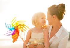 Moeder en babymeisje die kleurrijke windmolen houden Stock Fotografie