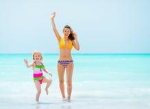 Moeder en babymeisje die met hand golven Royalty-vrije Stock Afbeeldingen