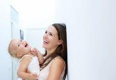 Moeder en babymeisje die samen lachen Stock Fotografie