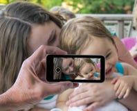 Moeder en babymeisje in smartphonemomentopname royalty-vrije stock afbeeldingen