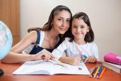 Moeder en daughter do homework thuis stock afbeelding