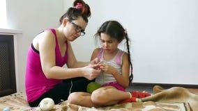 Moeder en dochter belast met breiend meisje en vrouwenhandwerk stock video
