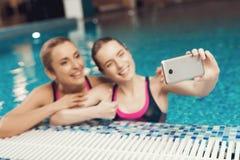 Moeder en dochter bij grens die van pool selfie bij de gymnastiek nemen Zij kijken gelukkig, modieus en geschikt stock afbeelding