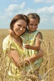 Moeder en dochter bij het tarwegebied Stock Afbeeldingen