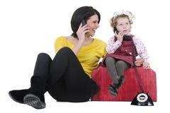 Moeder en dochter bij telefoon Stock Afbeelding