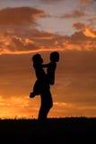 Moeder en dochter bij zonsondergang. Stock Fotografie