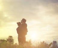 Moeder en dochter bij zonsondergang het letten op op hemel stock afbeeldingen