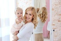 Moeder en dochter binnen met spiegel stock afbeelding