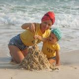 Moeder en dochter de bouwzandkasteel op het strand Stock Foto