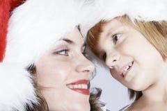 Moeder en Dochter in de Hoeden van de Kerstman Stock Afbeeldingen