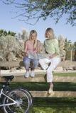 Moeder en Dochter de Kaart van Sit On Fence Looking At Royalty-vrije Stock Afbeeldingen