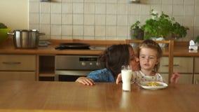 Moeder en dochter in de keuken Het mamma geeft de meisjesmelk Een goede eetlust Het gezonde Eten stock videobeelden
