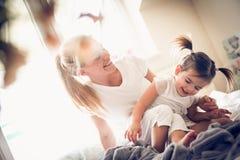 Moeder en dochter de ochtenden zijn speels stock foto