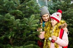 Moeder en dochter die bij markt onder Kerstbomen blijven Royalty-vrije Stock Afbeeldingen