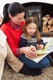 Moeder en Dochter die binnen en Boek ontspannen lezen royalty-vrije stock afbeeldingen