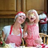 Moeder en dochter die chrtistmaskoekjes maken Stock Foto's