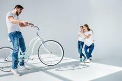 Moeder en dochter die de emotionele mens bekijken die pret met fiets hebben stock foto