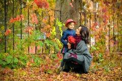 Moeder en dochter die in de herfst spreken Stock Afbeelding