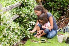 Moeder en dochter die in de tuin werken Royalty-vrije Stock Foto's