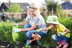 Moeder en dochter die in de tuin werken Stock Afbeeldingen