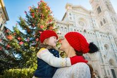 Moeder en dochter die dichtbij Kerstboom in Florence koesteren royalty-vrije stock afbeelding