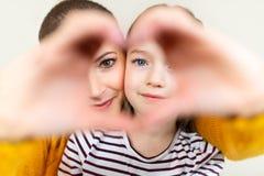 Moeder en dochter die door hart gestalte gegeven de handgebaar van het liefdesymbool kijken Familie, liefde, samenhorigheidsconce royalty-vrije stock foto
