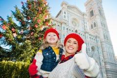 Moeder en dochter die duimen in Kerstmis Florence tonen stock afbeeldingen