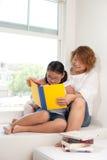 moeder en dochter die een boek lezen Stock Foto